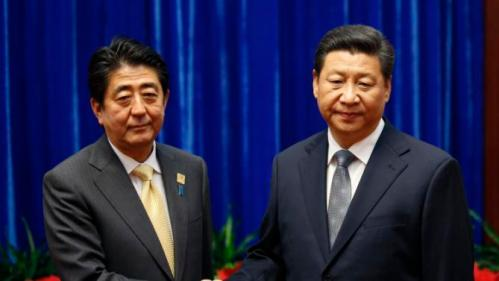China's President Xi Jinping (R) shakes hands with Japan's Prime Minister Shinzo Abe (L) at the Great Hall of the People on the sidelines of the Asia-Pacific Economic Cooperation (APEC) Summit in Beijing on November 10, 2014.  Top leaders and ministers of the 21-member APEC grouping are meeting in Beijing from November 7 to 11.   AFP PHOTO / POOL / Kim Kyung-Hoon