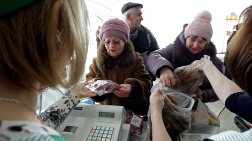 "People buy goods at a shop of the ""Russia"" collective farm in the settlement of Grigoropolisskaya, northwest of the southern city of Stavropol, February 17, 2015. Officials in both Russia and Ukraine are considering tougher trade protections to keep food prices from spiralling as their currencies collapse, with Moscow taking more aggressive steps than Kiev to control exports. Picture taken February 17, 2015.   REUTERS/Eduard Korniyenko (RUSSIA - Tags: FOOD AGRICULTURE CONFLICT BUSINESS CIVIL UNREST POLITICS) - RTR4QZXJ"